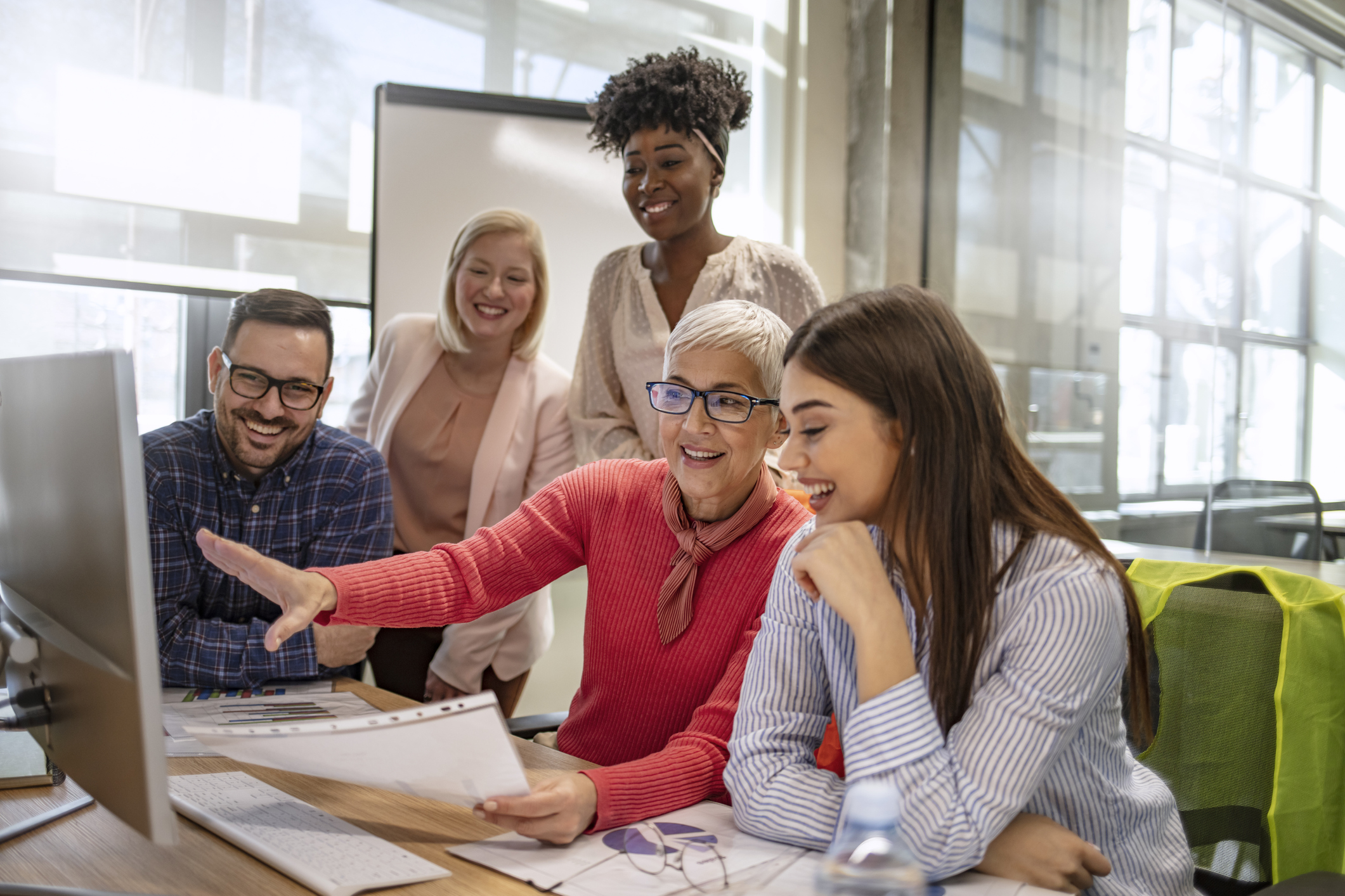 Senior designer giving some new ideas about project to her partners in conference room. Business people discussing over new business project in office. Group of businesspeople or designers work with new startup project in office